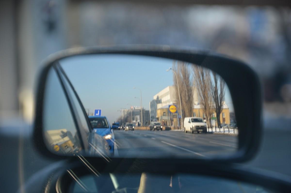 """Nauka do Egzaminu na Prawo Jazdy. Zdjecie lusterek do nauki jazdy, w górnym lusterku jadący z tyłu samochód nauki jazdy z elką """"L"""" na dachu"""