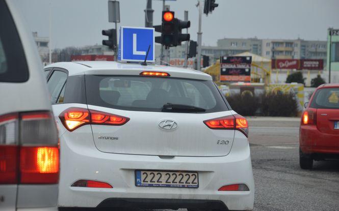 """Widoczny od tyłu biały samochód nauka jazdy Warszawa, marki Hyundai i20 z niebieskim symbolem elki """"L"""" na dachu. Oczekujący na możliwośc ruszenia, na czerwonym świetle dla jego kierunku jazdy."""