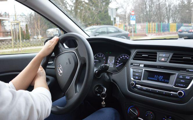 Szkoła jazdy Warszawa podczas szkolenia kursanta, dwie rece na kierownicy podczas wykonywania manewru skretu w lewo.