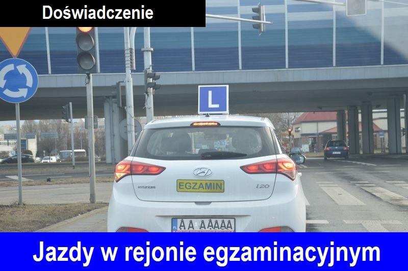Biały samochód egzaminacyjny nauka jazdy Warszawa z symbolem elki %22L%22 na dachu, widoczny od tyłu, na tylnych drzwiach napis%22egzamin%22, stojący przed czerwonym światłem na skrzyżowaniu. Na dole zdjecia napis %22Jazdy w rejonie egzaminacyjnym%22, na górze napis %22Doświadczenie%22.