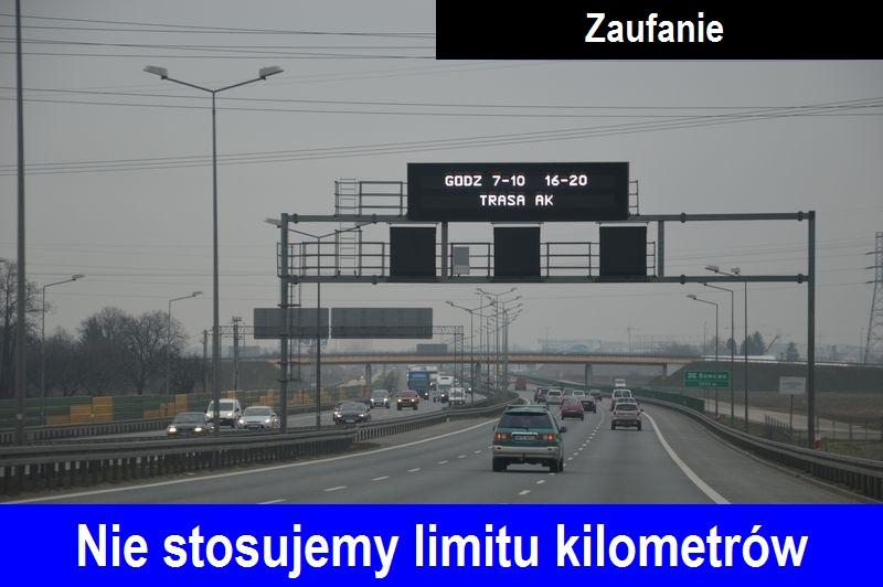 """Widok jadących samochodów trasą AK nauka jazdy w Warszawie, pochmurno. Na dole zdjecia napis """"Nie stosujemy limitu kilometrów"""", na górze napis """"Zaufanie""""."""