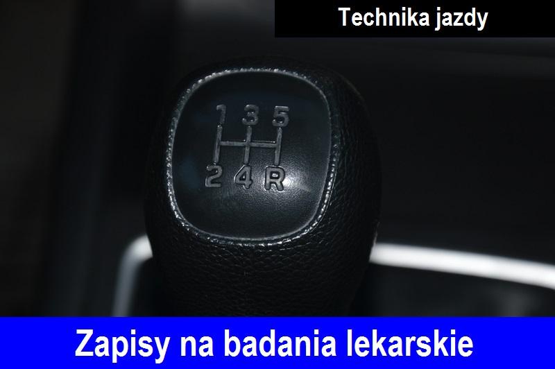 """Dźwignia zmiany biegów koloru czarnego, na dźwigni wytłoczony rysunek z informacją ułożenia poszczególnych biegów, w kaształcie litery H. Na dole zdjecia niebieski pasek, a na nim biały napis """"Zapisy na badania lekarskie"""", w prawym górnym rogu napis """"Technika jazdy""""."""