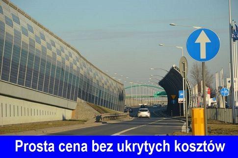 Znak nakaz jazdy prosto, po prawej stronie drogi Trasa Toruńska w Warszawie, po lewej bariera dźwiekochłonna. Na dole zdjecia niebieski pasek, a na nim biały napis %22Prosta cenabez ukrytych kosztów%22.