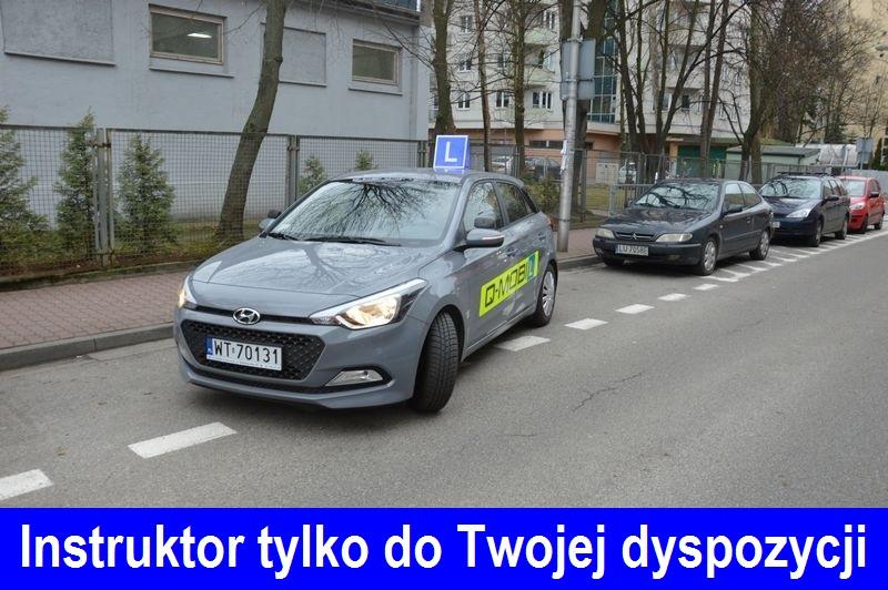 Parkowanie równoległe samochód Hyundai i20 koloru szarego, nauka jazdy Warszawa z symbolem elki %22L%22 na dachu. Q-Mobil.. Na dole zdjecia napis %22Instruktor tylko do Twojej dyspozycji%22
