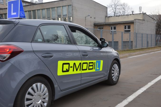 Samochód nauka jazdy z symbolem L na dachu i logo Q-Mobil na drzwiach stojący na placum naewrowym, w tle budynek szkoły.