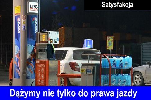 """Stacja benzynowa PKN ORLEN, tankowanie białego samochodu marki Skoda Fabia, nauka jazdy z symbolem elki """"L"""" na dachu. Na dole zdjecia napis """"Dążymy nie tylko do prawa jazdy"""", na górze napis """"Satysfakcja""""."""
